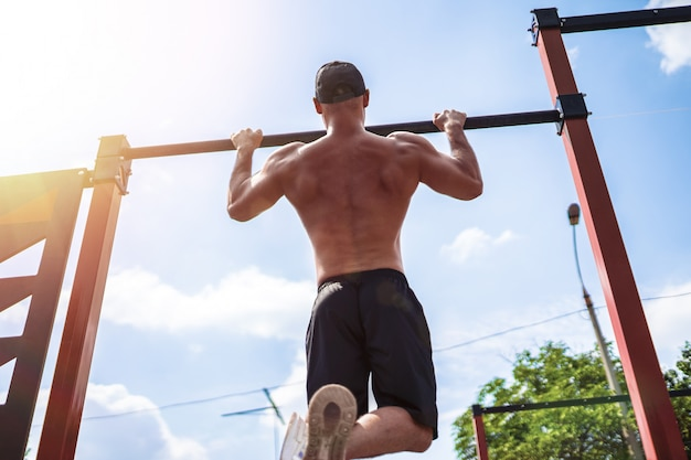 Brutal athletic man making pull-up exercises on a crossbar.