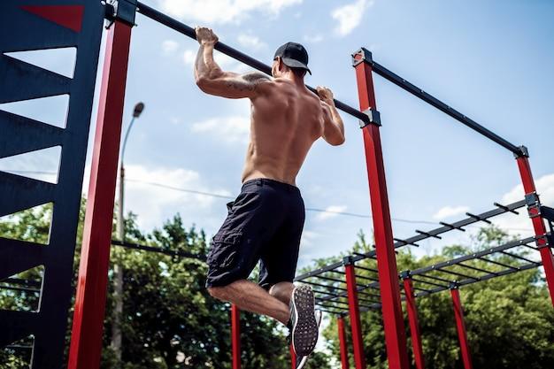 Брутальный спортивный человек делает подтягивающие упражнения на перекладине.