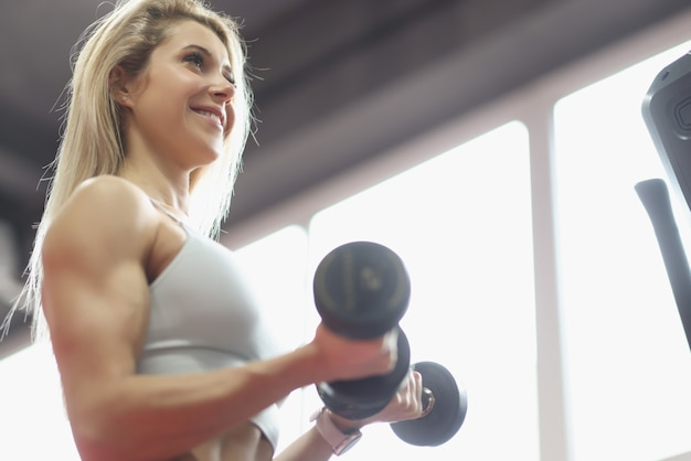 Brutal athletic woman pumps up muscles with dumbbells biceps workout concept