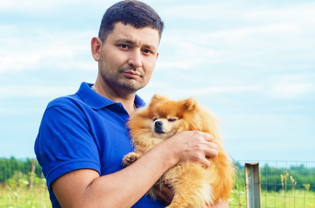 Brutal attractive man smiling and holding pomeranian spitz in hands. owner hugging the dog, spending leisure time together outdoors. pet adoption. friendship of human and animal