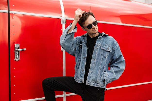 残忍な魅力的なトレンディな若い男は髪をまっすぐにします。街の金属の赤い壁の近くでポーズをとる黒いヴィンテージサングラスのファッショナブルな若者の服を着たハンサムな流行に敏感な男。ストリートチルドレンスタイル。