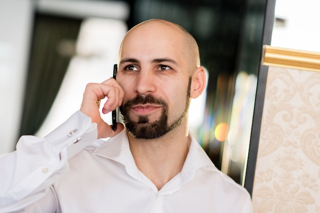 A brutal bald man talking on the phone.