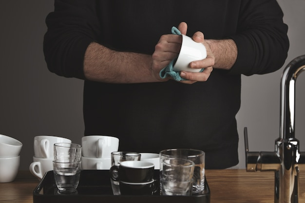 Brutal barista in black sweatshot behind thick wooden table dries clean blank white and transparent coffee, tea, whiskey cups and glasses with turqouise microfiber cloth in cafe shop.