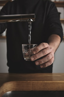 Brutal barista in black sweatshot behind thick wooden table fills small tranparent glass with water under silver metal tap in cafe shop.