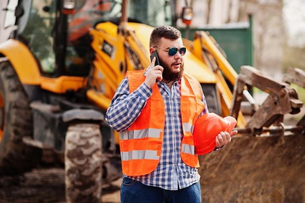 Brutal beard worker man suit construction worker in safety orange helmet, sunglasses against traktor with mobile phone at hand.
