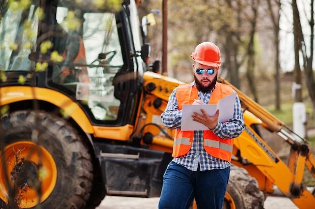 Brutal beard worker man suit construction worker in safety orange helmet, sunglasses against traktor with plan paper at hands.