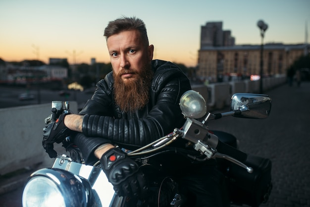 残忍なひげを生やしたバイカーがチョッパーでポーズ、正面図