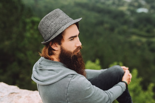 残忍なあごひげを生やした男は、美しい夏の風景を鋭く見ています。