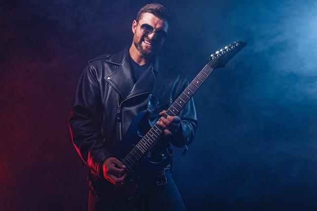 가죽 자켓과 선글라스의 잔인한 수염 난 헤비메탈 뮤지션이 연기와 함께 검은 색 전기 기타를 연주하고 있습니다.
