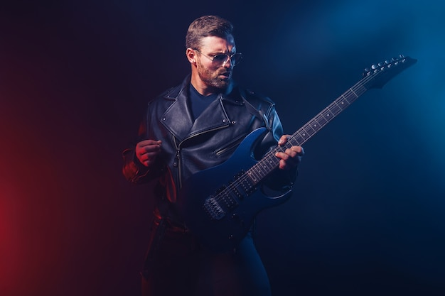 가죽 재킷과 선글라스의 잔인한 수염 난 헤비메탈 뮤지션이 블랙에 전기 기타를 연주하고 있습니다.