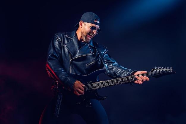 가죽 자켓과 선글라스를 쓴 잔인한 수염 난 헤비메탈 뮤지션이 블랙에 매우 감정적으로 전기 기타를 연주하고 있습니다.