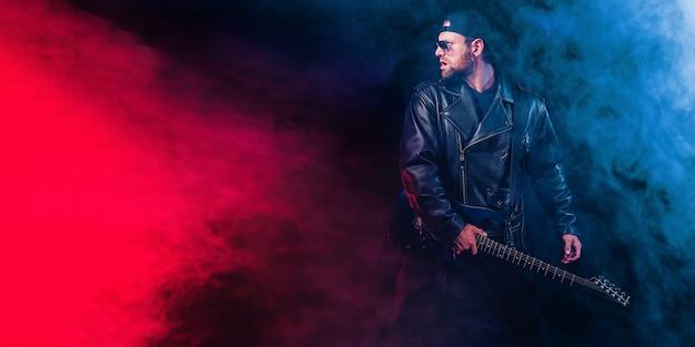가죽 자켓 모자와 선글라스의 잔인한 수염 난 헤비메탈 뮤지션이 블랙에 전기 기타를 연주하고 있습니다.