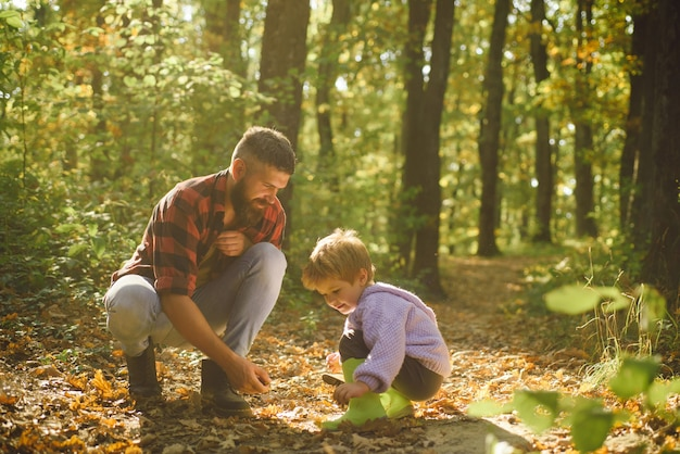 Брутальный бородатый мужчина и маленький мальчик наслаждаются осенней природой. семейные ценности. исследуй природу. концепция страсти к путешествиям. хипстерский бородатый папа с милым сыном проводят время вместе в лесу. время для семьи. семейный досуг