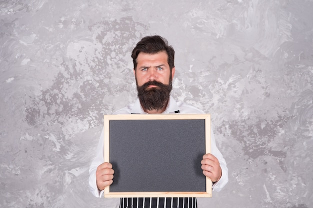 Жестокий бородатый шеф-повар, представляющий меню ресторана на пустой доске для рекламы места для копирования, рекламы.