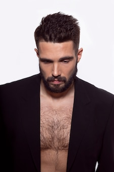Brutal bearded man posing in black suit, with naked torso