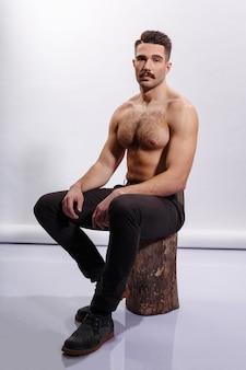 残忍なひげを生やした男、上半身裸、筋肉のある体、上腕二頭筋、上腕三頭筋、木の幹、白い背景の上に座っています。垂直ビュー。