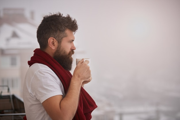 Brutal bearded man standing outside with red towel on shoulders, holding cup with steaming hot drink. young handsome carefree man enjoying a cup of coffee while looking outside, good morning.