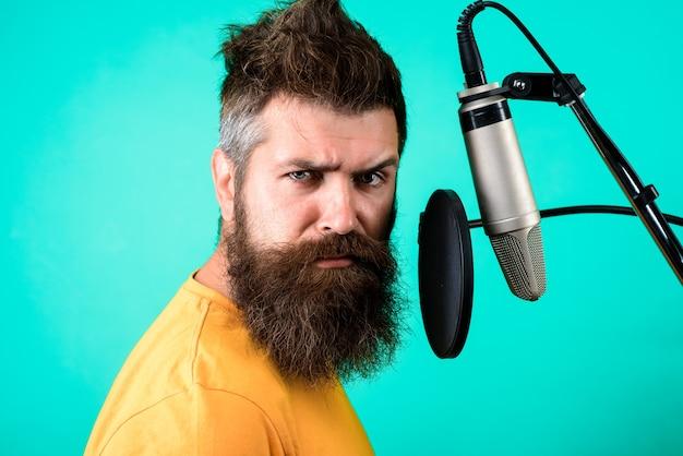Брутальный бородатый певец с микрофоном на сцене бородатый мужчина поет в микрофон концертмузыка