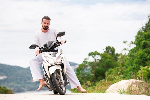 Брутальный байкер с бородой в белом сидит на мотоцикле. солнечный день в горах.
