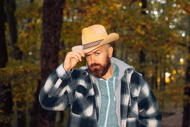 Brutal brunette bearded man in warm hat in the woods on a background of trees stylish hipster man in...