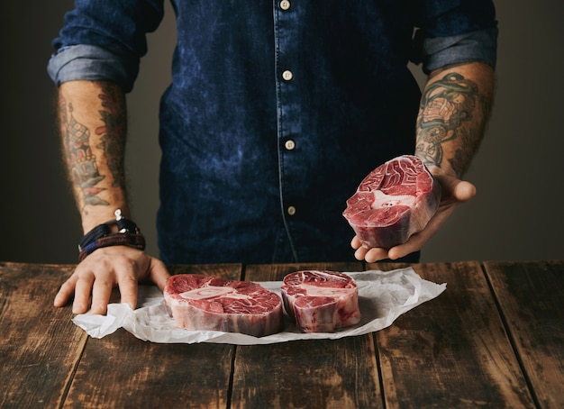 Brutal butcher with tattooed hands offers a piece of great raw meat steak on camera, other steaks in white craft paper on vintage old wooden grunge table. unrecognizable