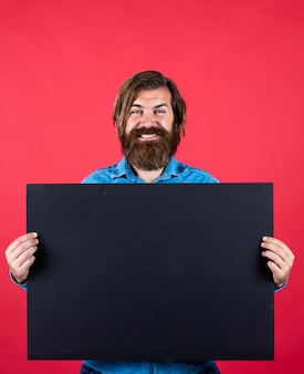 Brutal caucasian hipster hold paper shit, copy space. human emotions. unshaven guy with groomed long hair. barbershop and hairdresser. male beauty and fashion. happy bearded man.