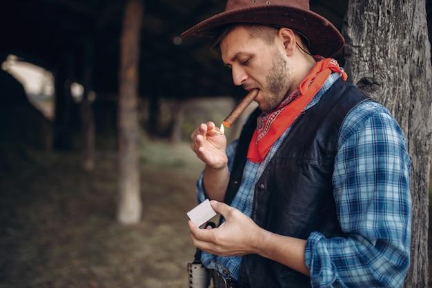残忍なカウボーイがマッチで葉巻を照らす、テキサス牧場、西洋。ヴィンテージの男性人が野生の西のライフスタイルの農場でリラックス