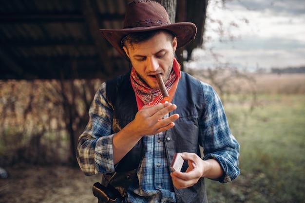 Брутальный ковбой зажигает сигару спичками