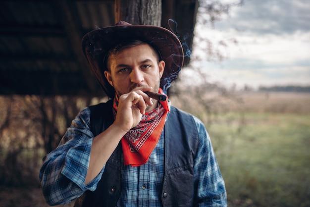 Брутальный ковбой курит сигару, культура дикого запада