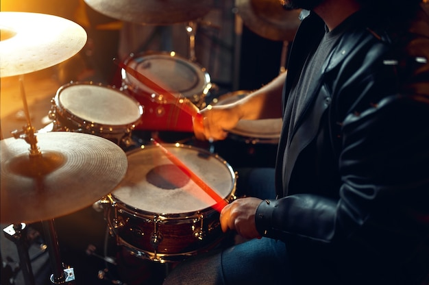 ドラムキットの後ろにいる残忍なドラマー、ステージで演奏する音楽。ロックバンドの演奏またはガレージでの繰り返し、楽器を持った男、ライブサウンドパフォーマー