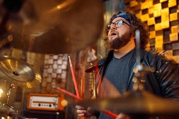 ドラムキットで演奏する残忍なドラマー、ステージで演奏する音楽。ロックバンドの演奏またはガレージでの繰り返し、楽器を持った男、ライブサウンドパフォーマー