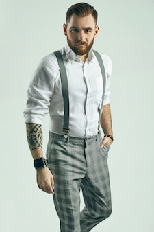 Brutal elegant man in gray classic pants and suspenders isolated on white