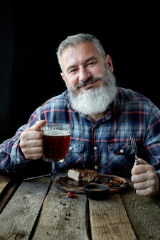 Brutal gray-haired adult man crazy about mustard steak and beer,  holiday, festival, oktoberfest or st. patrick's day