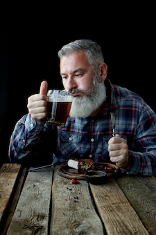 Brutal gray-haired adult man crazy about mustard steak and beer