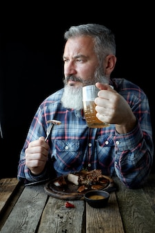 Brutal gray-haired adult man with a beard eats mustard steak and drinks beer