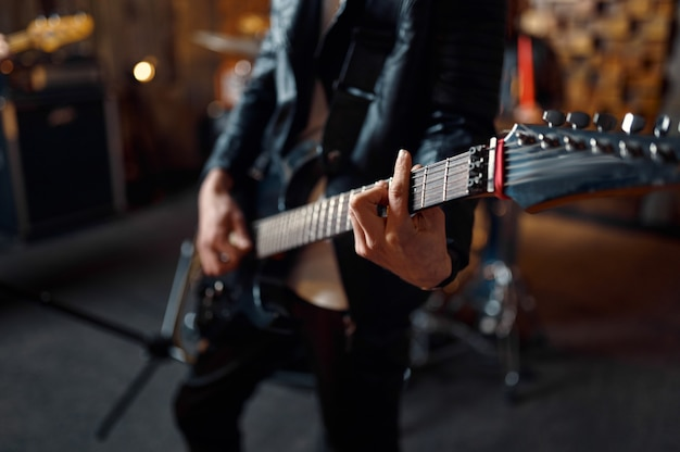 エレクトリックギターを持ち、ステージで音楽を演奏する残忍なギタリスト。ロックバンドの演奏またはガレージでの繰り返し、弦楽器を持った男、ライブサウンド