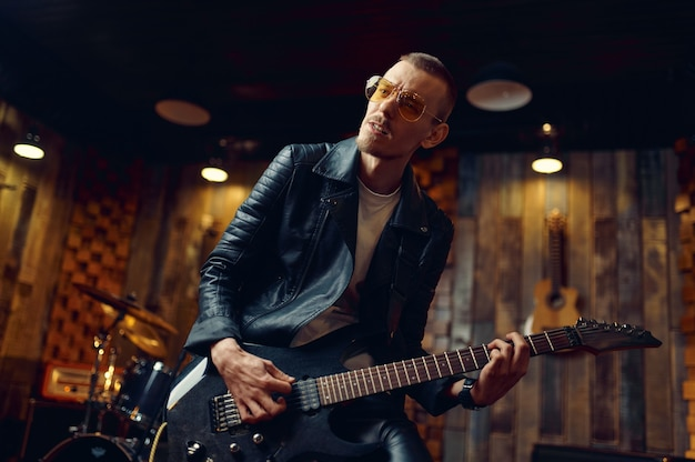 ステージでエレキギターを弾く残忍なギタリスト
