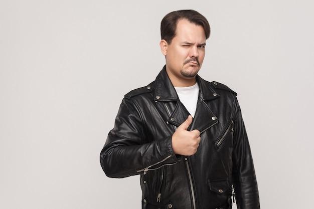 黒のジャケットを着た残忍な男がウィンクし、親指を立ててカメラを見ています。灰色の背景で撮影したスタジオ