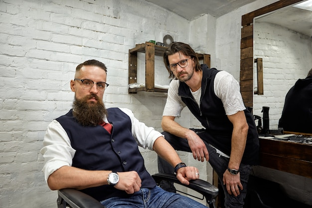 Brutal guy in modern barber shop. hairdresser makes hairstyle a man with a long beard. master hairdresser does hairstyle by scissors and comb