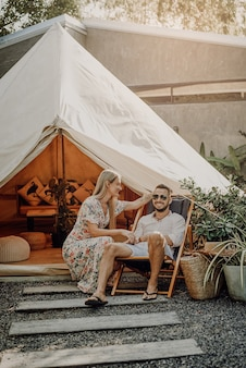 Brutal guy with sunglasses sits on chair and looks at camera. beautiful woman looks at her husband. sweet couple pose in background of their camp.