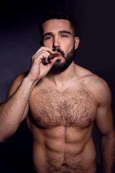 Brutal handsome bearded man with naked torso, smoking a cigarette