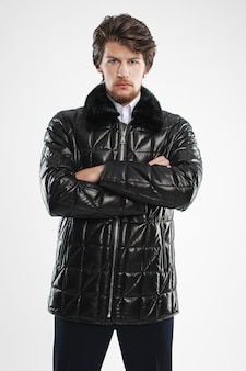 Brutal handsome unshaven man with beard and moustache in waterproof coat with fur collar