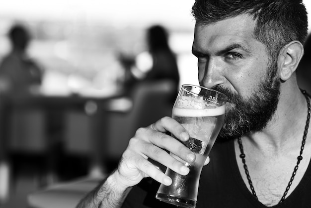 残忍な流行に敏感なひげを生やした男は、バーのカウンターに座っています。ビールのパブとバー