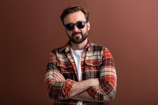 Brutal hipster handsome stylish bearded man on brown
