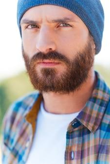 残忍な表情。屋外に立っているときにカメラを見ているハンサムなひげを生やした男の肖像画
