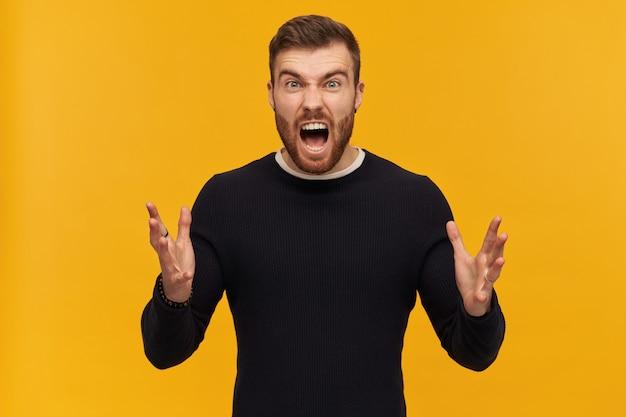 갈색 머리와 수염을 가진 잔인한 남성, 불만족스러운 남자. 피어싱이 있습니다. 검은 스웨터를 입고. 분노에 손을 들고 비명을 지른다. 노란색 벽 위에 절연