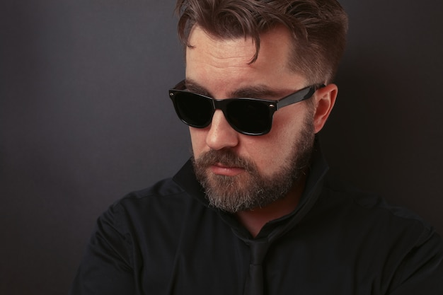 A brutal man in a black suit and sunglasses.