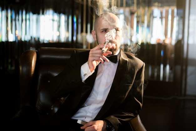 A brutal man in a dress coat smokes a cigar.