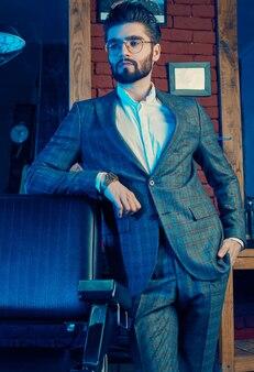 Brutal man in elegant suit and glasses in barbershop