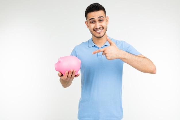 Брутальный мужчина в синей рубашке держит копилку и указывает пальцем на него на белом фоне с копией пространства